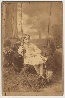 An unidentified girl is seated on a swing.  She is probably related to James White