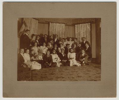 A group of unidentified people at the house of James G. White