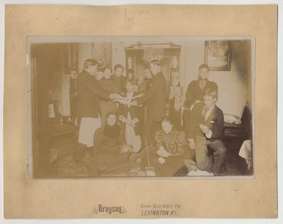 A group of unidentified people at a party and candy pulling at the house of James G. White, on the corner of Maxwell Street and Harrison Avenue