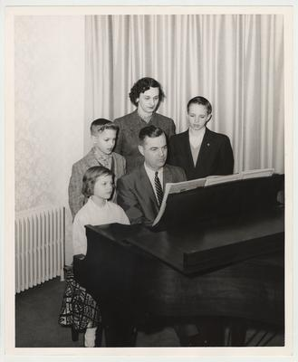 From the left:  Joe (standing); Betty (standing); Frank Dickey Jr. (standing); Ann (sitting); and President Dickey (seated).  The family is gathered around a piano.  Received by Public Relations on August 17, 1957