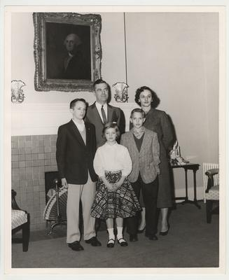 A Dickey family photograph taken in front of a fireplace.  Front row from the left:  Frank Dickey Jr., Ann, and Joe.  Back row from the left:  President Dickey and his wife Betty