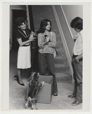 Mrs. Singletary and her daughter Kendall are on the Maxwell Place staircase with a dog and a kitten.  They are talking to an unidentified young man