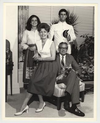 President Singletary with his family and their dog Butch in Maxwell Place.  President Singletary is seated and holding the dog, Gloria is on the arm of the chair, and Kendall and Scott (in his Navy uniform) are standing behind the chair