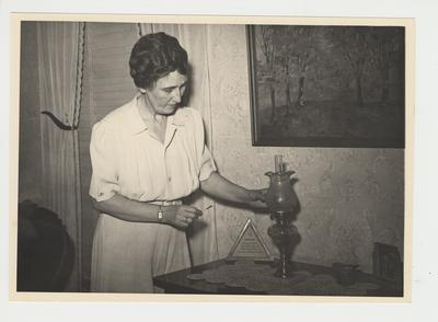Nell Donovan is lighting a lamp