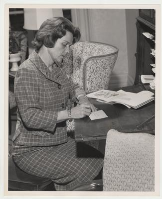 Rosanel Oswald is writing a note on a secretary or desk in the Maxwell Place library or family room