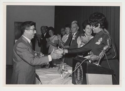 Dr. Albert Levy is shaking hands with an unidentified woman while Gloria Singletary (third from right) and Bert Combs (fourth from right) are clapping