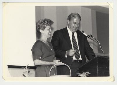 Gloria Singletary stands at a podium with Terry Mobley, head of development and former basketball player (1963 - 1965)