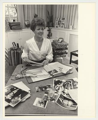 Gloria Singletary is placing clippings in her husband, President Singletary's scrapbook