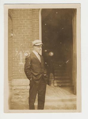 An unidentified man is standing in front of a building