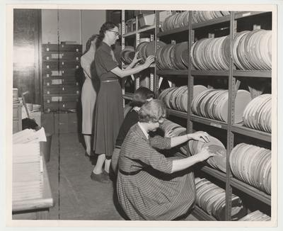 Ruby Watts (far left), Mrs. June Flanery (second from left), Annette Andrews (center), and Mrs. Lagatha Monroe (far right) are looking for films in the Film Library for the University Extension program at the University of Kentucky.  University Extension is the forerunner of distance learning