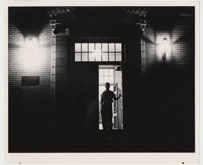 An unidentified man is walking out of the Margaret I. King Library at night