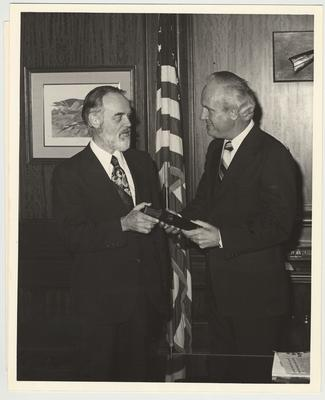 Julian M. Carroll, Governor of the state of Kentucky, (right) is being given a copy of the