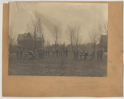 Men in uniforms with cannons are in front of J. K. Patterson's house.  Patterson's house was later torn down in order to build the Patterson Office Tower and White Hall Classroom Building
