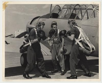Three unidentified men are standing beside an Army plane.  Two of the men are wearing boxing gloves