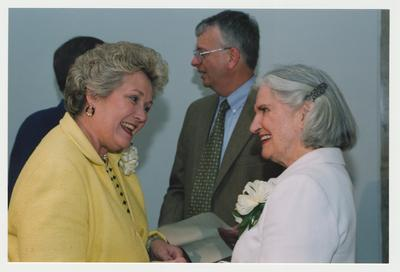 Patricia B. Todd (left) is talking with Loretta Brock (right)  at Dr. Thomas D. Clark's 100th birthday celebration at Young Library.  William J. Marshall, Director of Special Collections and Archives is standing near Patricia Todd and Loretta Brock