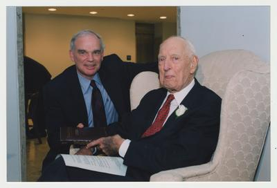 Provost Michael Nietzel (left) is handing Thomas Clark (right) a book at Dr. Thomas D. Clark's 100th birthday celebration at Young Library