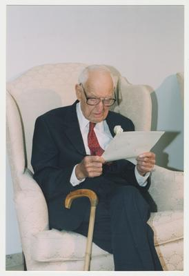 Dr. Thomas D. Clark is sitting and reading during his 100th birthday celebration at Young Library