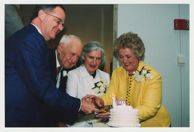Patricia Todd (right), Loretta Brock (second from right), and President Todd (left) are helping Thomas Clark (second from left) cut his birthday cake at Dr. Thomas D. Clark's 100th birthday celebration at Young Library
