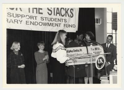 Unidentified women of Alpha Delta Pi are giving an oversized check for 10,000 dollars to the Student Library Campaign