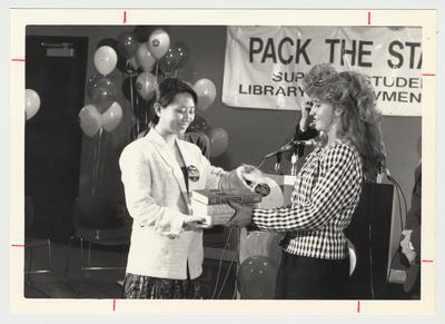 Chai Ling (left) symbolically accepts the first textbooks donated to the library from Diana Goetz (right) who graduated from UK in the spring of 1991 with a degree in Business