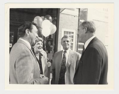 Athletic Director C. M. Newton (right) is talking with Vice President Gene Williams (second from right); Carolyn Curry (second from left), Professor of Women's Studies and spouse of Football Coach Bill Curry; and President Charles Wethington (right)