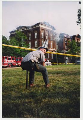 An unidentified man is seated outside of the Administration / Main Building during the fire