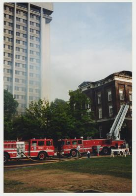 Two fire trucks are outside of the Administration / Main Building during the fire