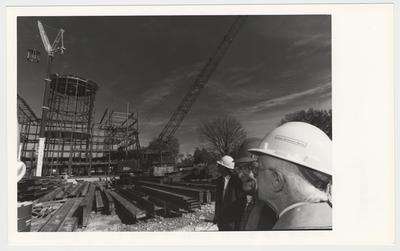 William T. Young in white construction hat and other men are watching the construction of the William T. Young Library