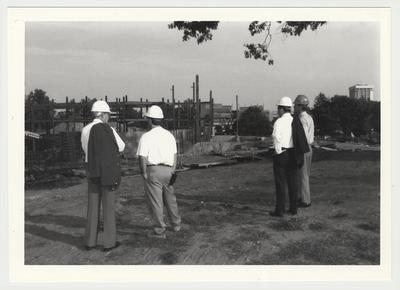 President Charles Wethington (second from right) is watching the construction of the William T. Young Library with three unidentified men