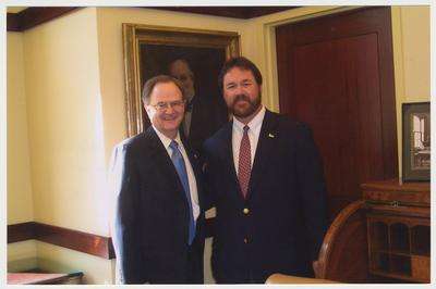 President Lee Todd (left) and  David Doss (right), with Messer Construction Company, are in the President's Conference room in the Main Building.  They are both standing in front of the painted portrait of President James K. Patterson