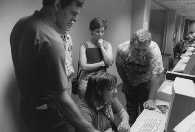 Five unidentified people are looking at a computer in the computer lab