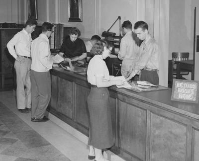 Circulation Desk--Circulation Desk--Great Hall, second floor; woman behind desk is Thelma Rogers, man behind desk (facing) is Ed Hall, man behind desk (back) is Ray Adams, and the woman on the other side of the desk is Sally Poundstone