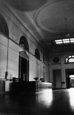 An unidentified woman is seated at the circulation desk in the Great Hall in King Library