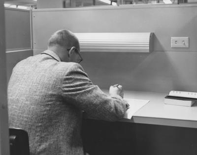 A man studying in the open stacks area in the M. I. King Library