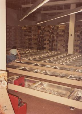A color photo of an unidentified person building shelves for periodicals and serials on the second floor of Margaret I. King North Library. Photographer: Terry Warth