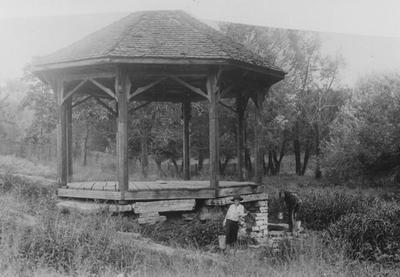 One man collecting water from the spring with buckets and a boy is facing the camera with a bucket