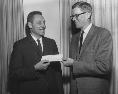 Dr. John H. Githens (left), chairman of the Pediatric Department accepts $5,000 in research funds from W. H. Rennie, Jr. Received April 27, 1962 from Public Relations. Photographer: Mack Hughes