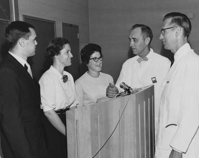 Various unidentified people are gathered around a podium; second woman on the right is R. Eubank. Herald-Leader Photograph