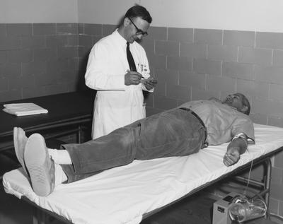 Dr. John A. Koepke tends to Frank Abell, the first blood donor at UK's new hospital. Received April 23, 1962 from Public Relations