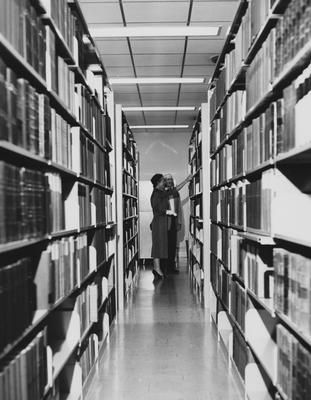 Two unidentified people are looking at books in the library at the dedication of the Medical Center