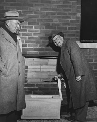 Man on the right is possibly Bernie Shively, athletics director, at Memorial Coliseum placing mortar for the 1949 - 50 cornerstone. Photographer: Ben L. Williams Jr