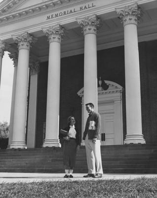 Lowell Hughes standing with and unknown female in front of Memorial Hall. Received October of 1957 from Public Relations
