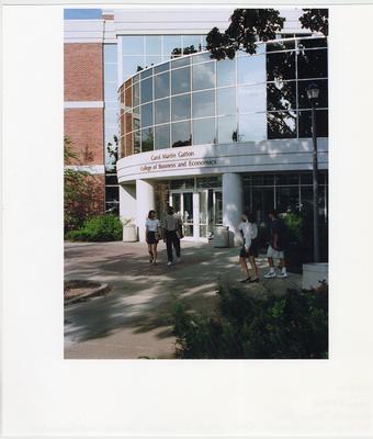 Unidentified men and women are walking past the Carol Martin Gatton College of Economics Building