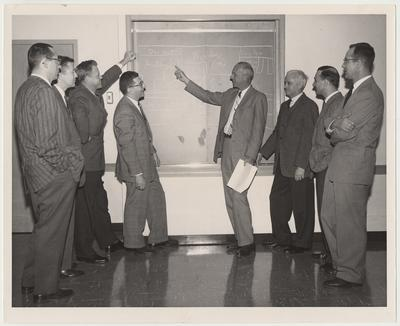 Members of the Committee on Educational Policy and Curriculum discuss the number of hours to be devoted to each area of study.  From the left:  Dr. Alan Ross, Dr. Robert E. McCafferty, Dr. William Knisely, Dr. Robert Straus, Dean William R. Willard, Dr. Joseph Parker, Dr. Edmund Pellegrino, and Dr. George Schwert