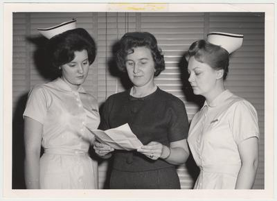 Two members of the first class of the College of Nursing look at a paper held by a third woman