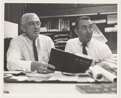 Mr. Howard, Chief Engineer of the Medical Center, holds a notebook in front of an unidentified man