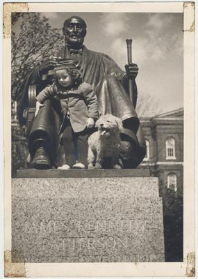 An unidentified little girl and her dog are standing on the Patterson Statue