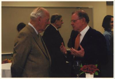 Ted Bassett (left), former director of Keeneland Racetrack, listens to an unidentified man