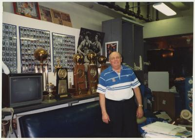 Bill Keightley, UK basketball equipment manager, is standing in front of trophies