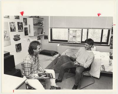 Two young men read magazines in a dorm room in Keeneland Hall